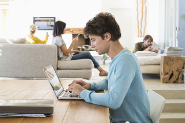 Man using a laptop with his friends using electronic gadgets in background