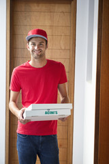 Portrait of a smiling deliveryman delivering pizza