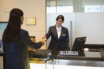 Businesswoman paying with a credit card at the hotel reception counter