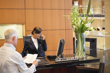 Businessman reading a brochure with a receptionist talking on a telephone at the hotel reception counter