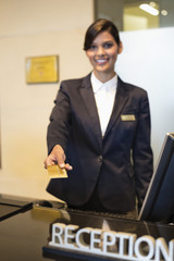 Receptionist holding a credit card and smiling at the hotel reception counter