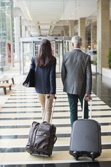 Business couple pulling suitcases in a hotel lobby