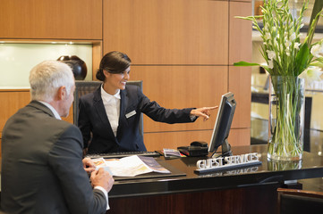 Receptionist pointing on a desktop pc with a businessman at the hotel reception counter