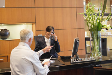 Receptionist talking on a landline phone with a businessman pointing at the hotel reception counter