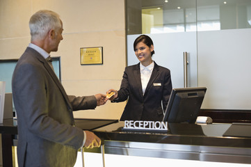 Businessman paying with a credit card at the hotel reception counter