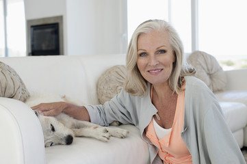 Portrait of a smiling woman stroking her dog lying on couch