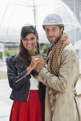 Portrait of a smiling couple under an umbrella