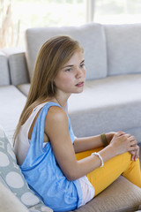 Girl sitting on a couch and looking upset