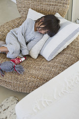 Girl sleeping on a wicker chair