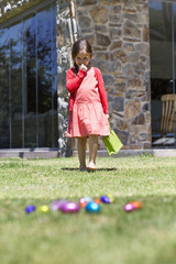 Girl looking at Easter eggs in a lawn