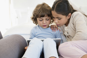 Girl looking at her brother using a digital tablet