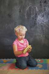 Girl playing with number puzzle in front of a black board