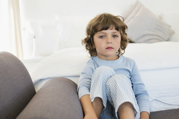 Portrait of a boy sitting on the bed looking sad