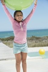 Girl holding a fitness ball on the beach