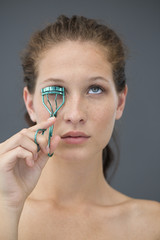Close-up of a woman curling her eyelashes with eyelash curler