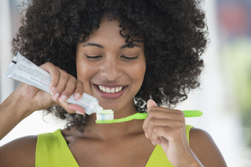 Woman squeezing out toothpaste on a toothbrush