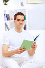 Young man at home with a book