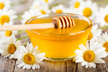 bowl of honey with daisy flowers