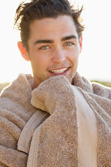 Portrait of a smiling man wrapped in a towel