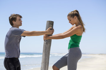 Man assisting a woman to exercise on the beach