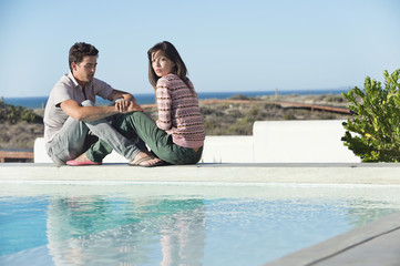 Romantic couple sitting at the poolside on the beach