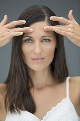 Portrait of a woman checking wrinkles on her forehead