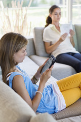 Girl using a digital tablet with her mother reading book at home