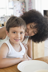 Portrait of a smiling boy sitting with his mother at a dining table