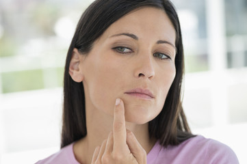 Woman checking wrinkles on her face
