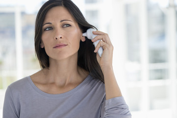Woman measuring her temperature with a digital thermometer