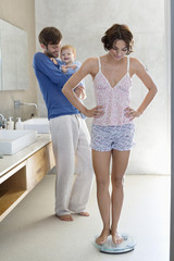 Woman measuring her weight on a weighing scale with her husband and son in bathroom