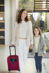 Woman walking with her daughter with a luggage