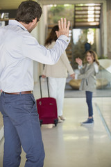 Man waving to his daughter leaving home