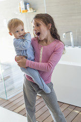 Girl carrying her brother and looking surprised in a bathroom