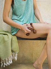 Mid section view of a woman massaging her leg with a massager