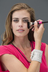 Portrait of a woman applying make-up with a make-up brush