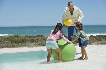 Man playing with his grandchildren on the beach