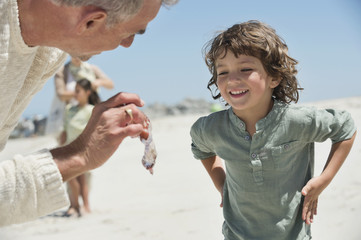 Man showing a jellyfish to his grandson on the beach