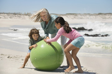 Woman playing with her grandchildren on the beach