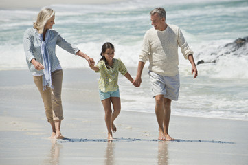 Girl walking with her grandparents on the beach