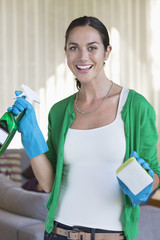 Portrait of a woman holding cleaning equipment and smiling