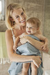 Smiling woman holding her baby in towel