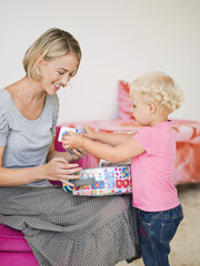 Smiling woman opening a box for her daughter