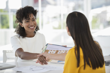 Real estate agent shaking hands with a woman