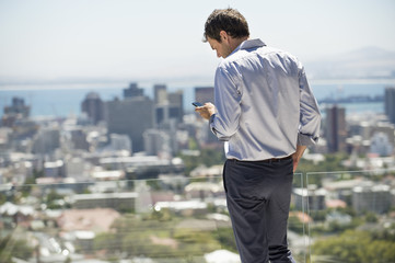 Man standing on the terrace using a mobile phone