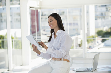 Businesswoman holding a digital tablet and smiling in an office