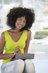 Portrait of a smiling woman using a digital tablet