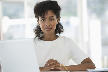 Portrait of a woman sitting in front of a laptop