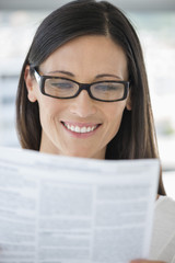 Close-up of a woman reading a document and smiling