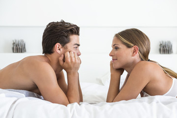 Couple lying face to face on the bed